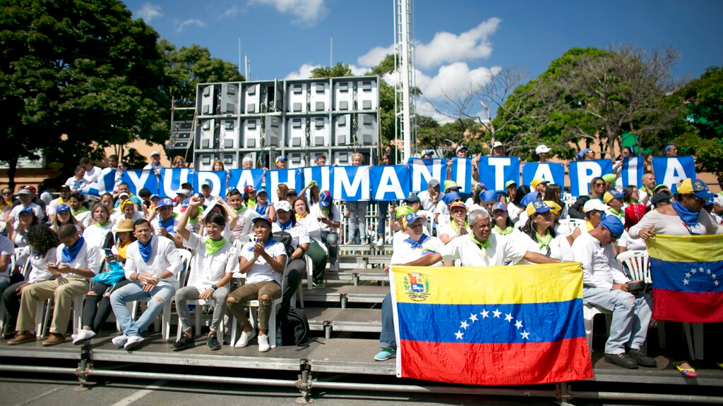 "People holds a sign that reads in Spanish ""Humanitarian Aid"" during an event to swear in nurses, doctors, professionals and others, as the group that will help with the arrival and distribution of humanitarian aid in Venezuela, in Caracas, Venezuela, Saturday, Feb. 16, 2019. (AP Photo/Ariana Cubillos)"