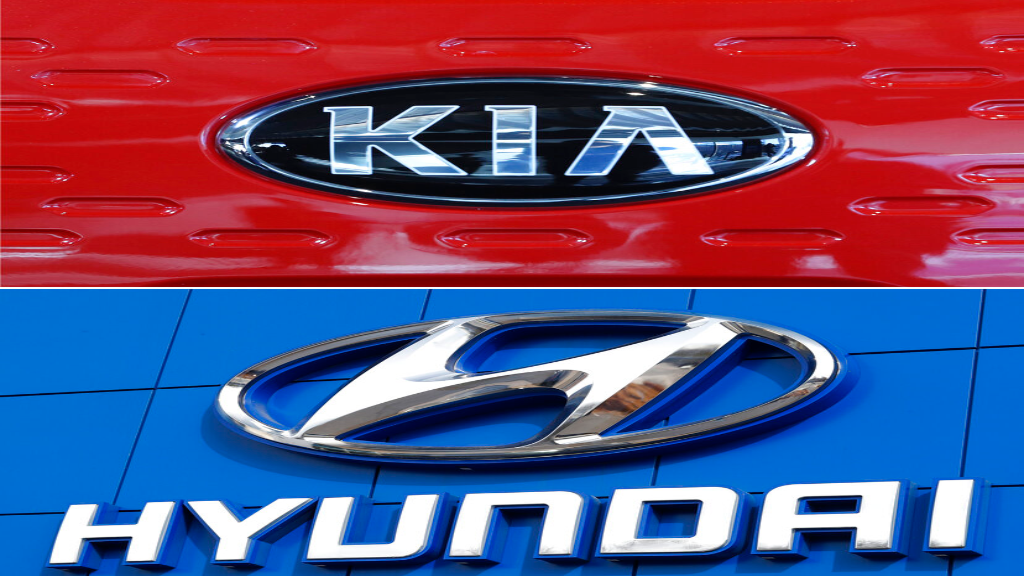 FILE- This combination of file photos shows the logo of Kia Motors during an unveiling ceremony on Dec. 13, 2017, in Seoul, South Korea, top, and Hyundai logo on the side of a showroom on April 15, 2018, in the south Denver suburb of Littleton, Colo., bottom. (AP Photo, File)