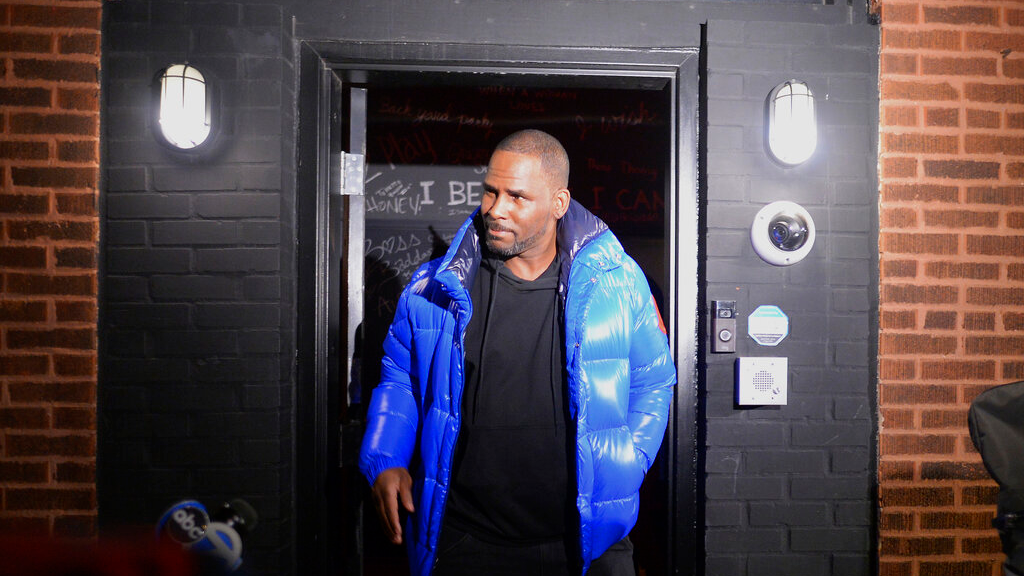 Musician R. Kelly leaves his Chicago studio on his way to surrender to police Friday night, Feb. 22, 2019. R&B star Kelly arrived Friday night at a Chicago police precinct, hours after authorities announced multiple charges of aggravated sexual abuse involving four victims, including at least three between the ages of 13 and 17. (Victor Hilitski/Chicago Sun-Times via AP)