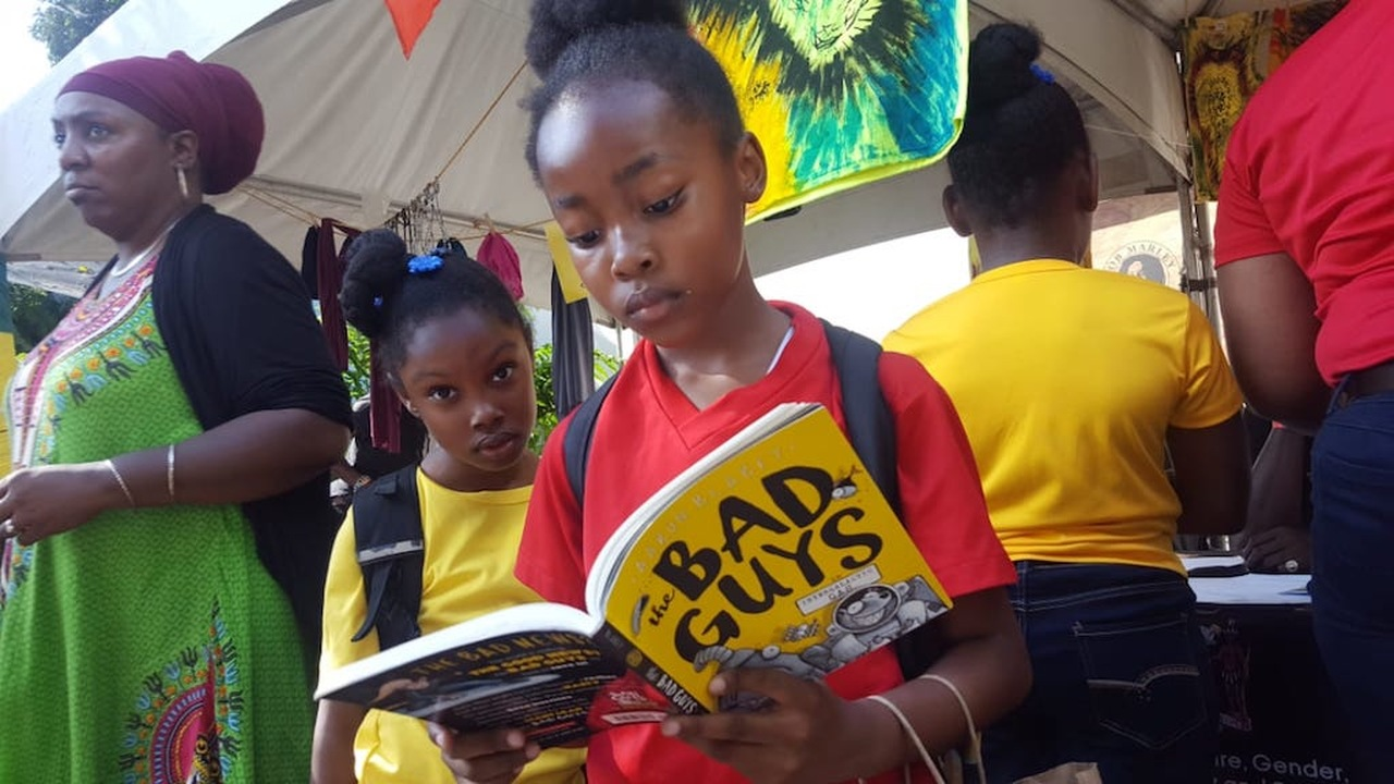 Jhenelle Barracks, a grade three student at Mount Moreland Primary & Junior High, reads a book during the Bob Marley 74th birthday celebration at the Bob Marley Museum. (PHOTO: Marlon Reid)