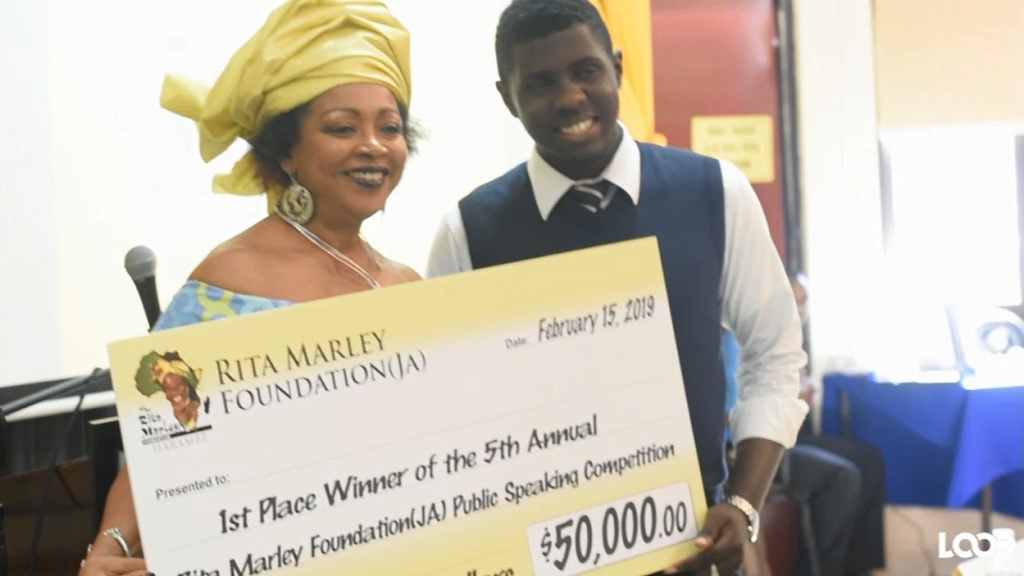 Winner of the 2019 Rita Marley Public Speaking Competition, Fabian Morris, was awarded the main prize of $50,000. Sharing in the moment is a judge in the competition, UWI lecturer, Professor Verene Shepherd.