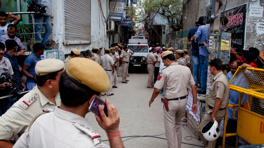 India Police next to the house where 11 bodies were found in Burari village, north Delhi, India, Sunday, July 1, 2018. Ten bodies, blindfolded by cotton and pieces of cloth, were found hanging from an iron grill used as a ventilator in the home's courtyard, while the body of a 70-year-old woman was lying on the floor of the house, said a police official who spoke on condition of anonymity, in line with department policy. (AP Photo/Rishabh R. Jain)