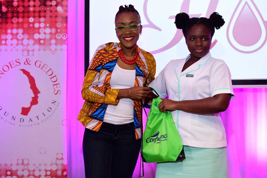 Shelly Ann Weeks, founder of HERFlow Foundation (left), presents a goodie bag courtesy of Confidence Sanitary Napkins to Ashli Bailey, student of Lister Mair Gibly School for the Deaf at the Writing HERStory youth empowerment conference.