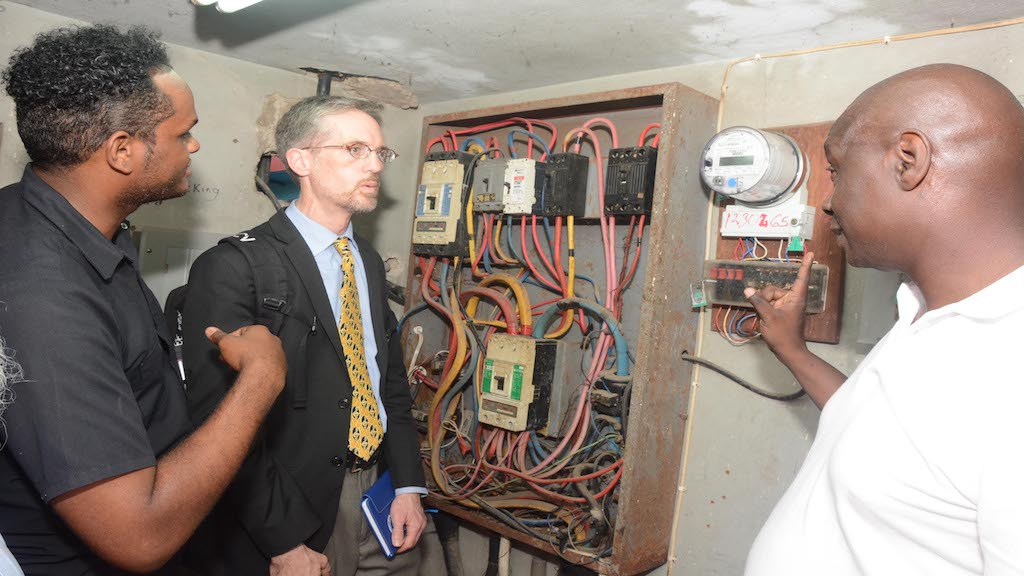 Principal of Camperdown High, Valentine Bailey (right) and the school's plant manager, Jason Cousins (left) show Wayne Groszko, Applied Research Scientist at Nova Scotia Community College in Canada, the electricity monitoring systems at the institution. Camperdown is one of 30 government facilities that will benefit under the Energy Management and Efficiency Programme.