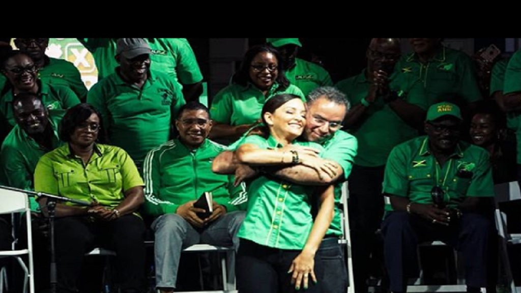 Ann-Marie Vaz and her 'Pums', husband Daryl Vaz, share a warm, public embrace on the political trail in East Portland recently. Looking on admiringly at left, (among others) is the wife and husband combination of Prime Minister Andrew Holness and wife, Juliet, both Members of Parliament (MPs) alongside Daryl Vaz. (Photo: Marlon Reid)