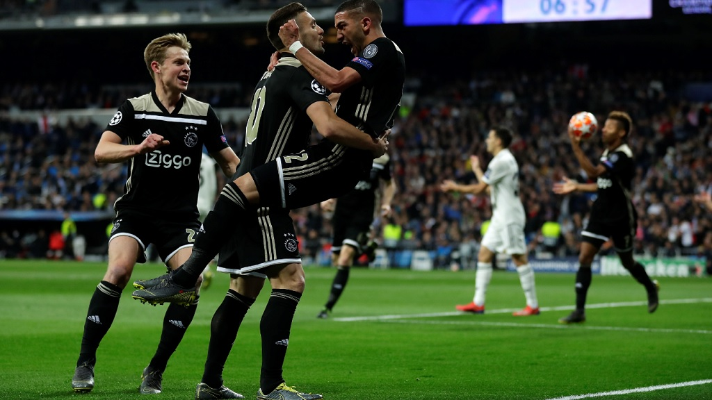 Ajax's Hakim Ziyech, right, celebrates scoring the opening goal during the Champions League football  match against Real Madrid at the Santiago Bernabeu stadium in Madrid, Spain, Tuesday, March 5, 2019.