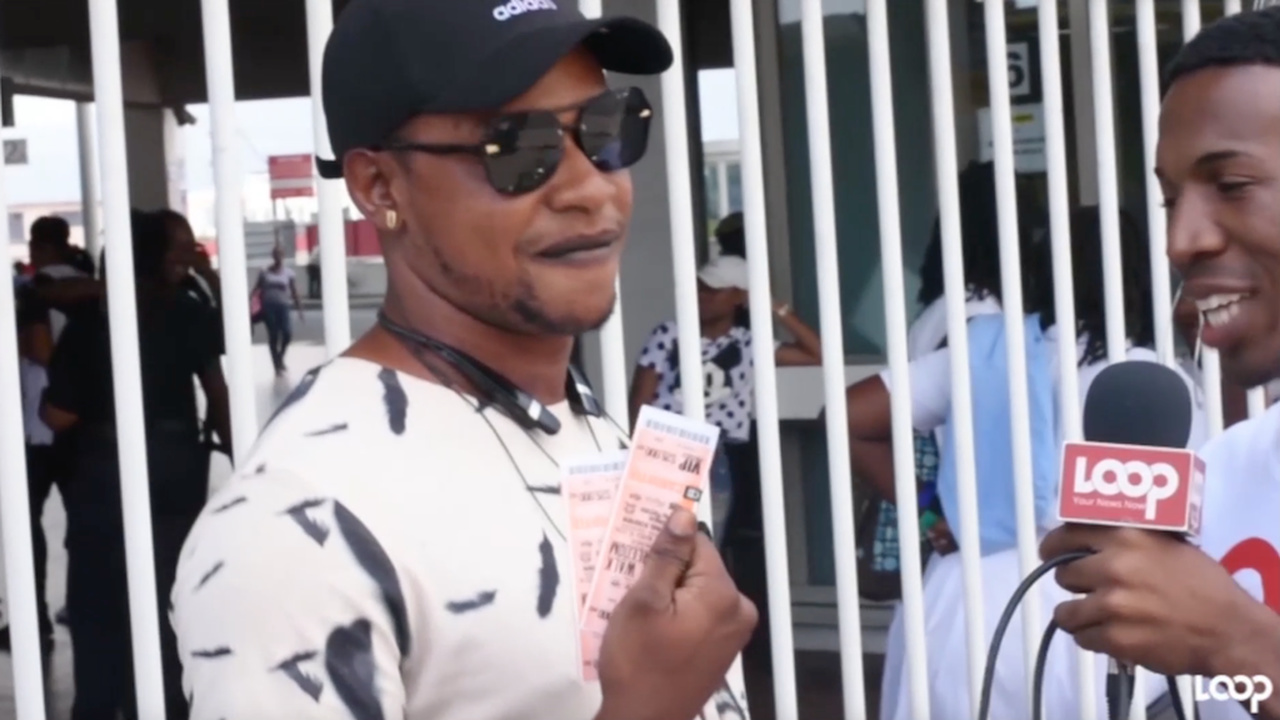 A Buju fan shows off the two VIP tickets he won during a giveaway by Loop News in Half-Way-Tree.