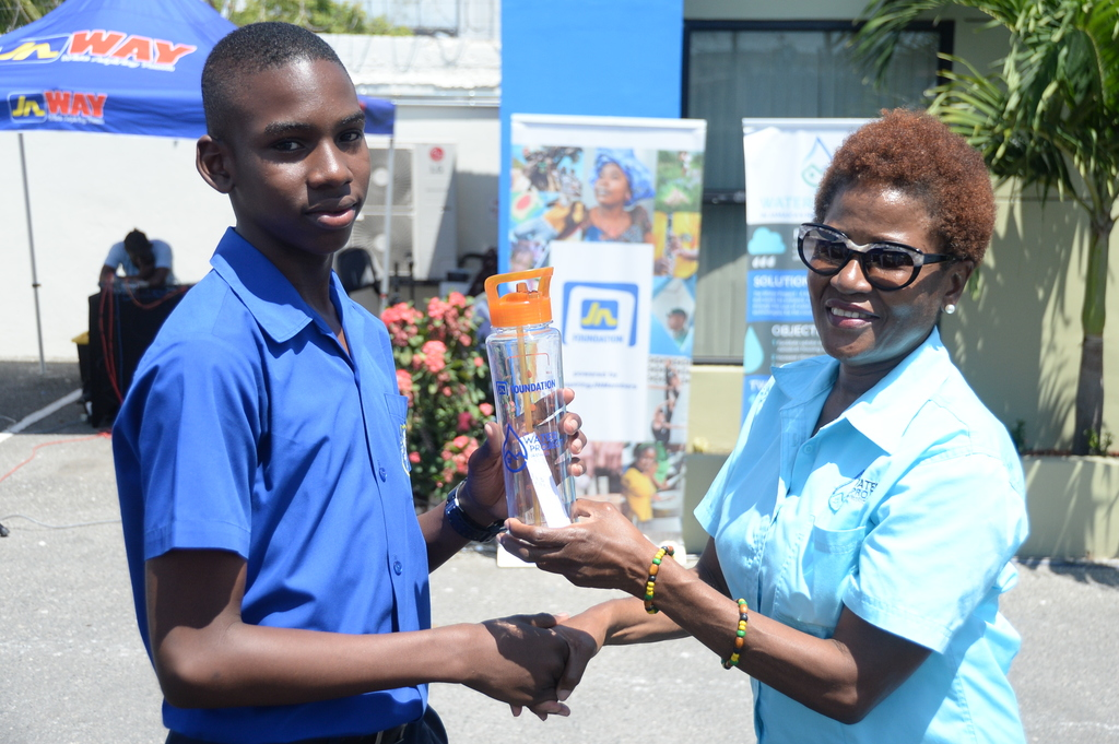Jacqueline Cameron (right), project manager of the Water Project Jamaica presents Patrick Frater, a student of Jamaica College with a water bottle after he answered a quiz correctly.