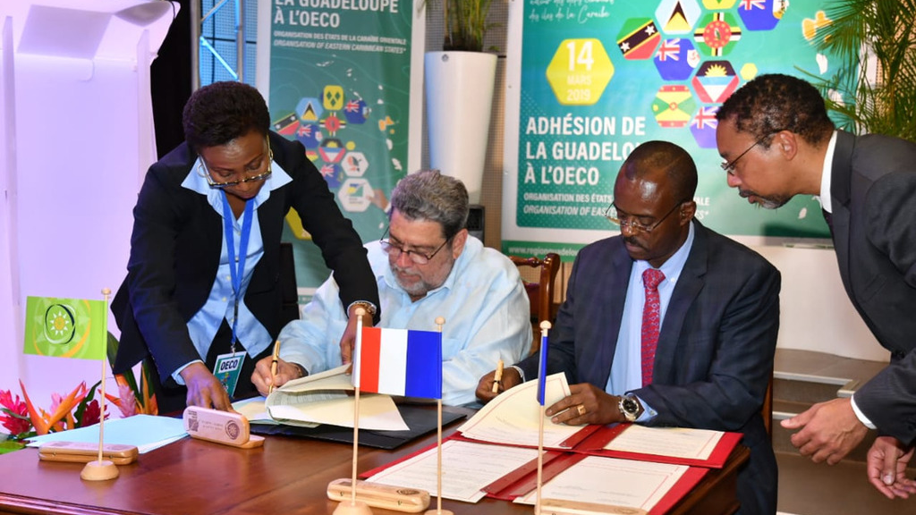 OECS Chairman Ralph Gonsalves and Ary Chalus, President of the Territorial Council of Guadeloupe, sign the agreement making Guadeloupe part of the OECS.