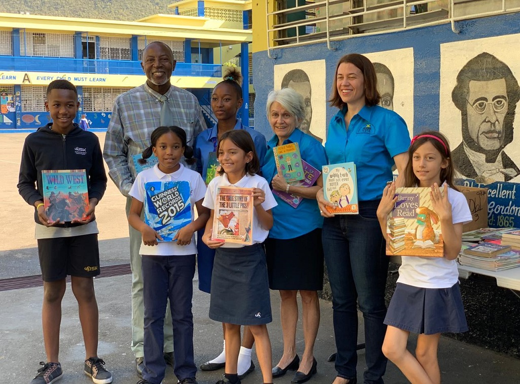 Noel Pennant (second left), principal of Windward Road Primary and Junior High and students are elated to receive book donations from students of  American International School of Kingston (AISK) ; Dr. Elizabeth Ward (third rigth), chair of the Violence Prevention Alliance (VPA) and Robin Heffernan (second right), project coordinator at the VPA.