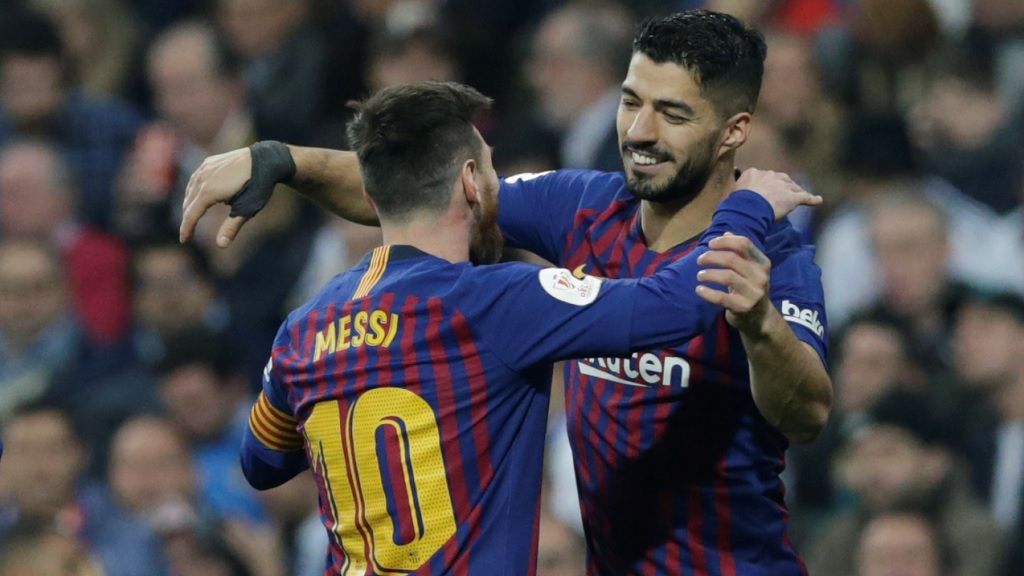 Barcelona forward Luis Suarez, right, celebrates with Lionel Messi after scoring his side's opening goal during the Copa del Rey semifinal second leg football match against Real Madrid at the Bernabeu stadium in Madrid, Spain, Wednesday Feb. 27, 2019.