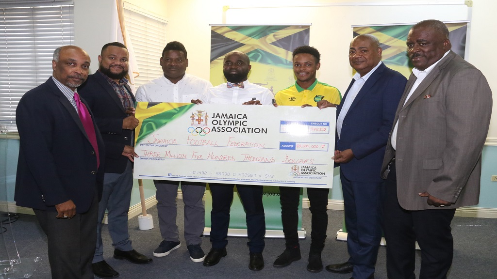 (From left) Jamaica Olympic Association (JOA) President, Christopher Samuda and General Secretary Ryan Foster, pose with Donovan Duckie, head coach, national Under-23 men's football team; assistant coach Merron Gordon; player Alex Marshall; Jamaica Football Federation (JFF) President Michael Ricketts and JOA Director, Raymond Anderson during the JOA's cheque presentation.