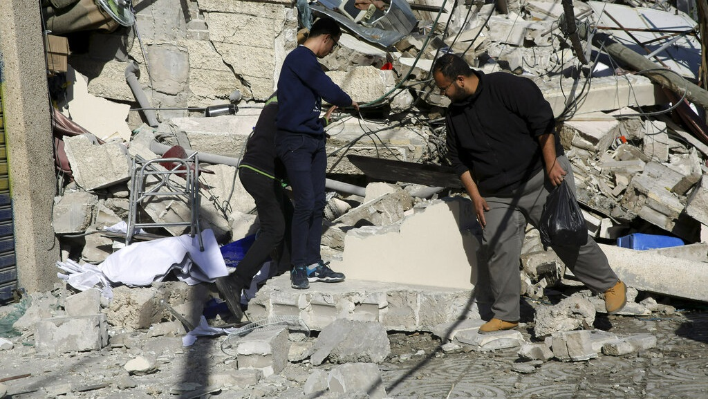 Palestinians inspect the damage of the destroyed multi-story building of Hamas-affiliated insurance company, in Gaza City, Tuesday, March 26, 2019. A tense quiet took hold Tuesday morning after a night of heavy fire as Israeli aircraft bombed targets across the Gaza Strip and Gaza militants fired rockets into Israel in what threatened to devolve into a major conflict two weeks before the Israeli election. (AP Photo/Adel Hana)