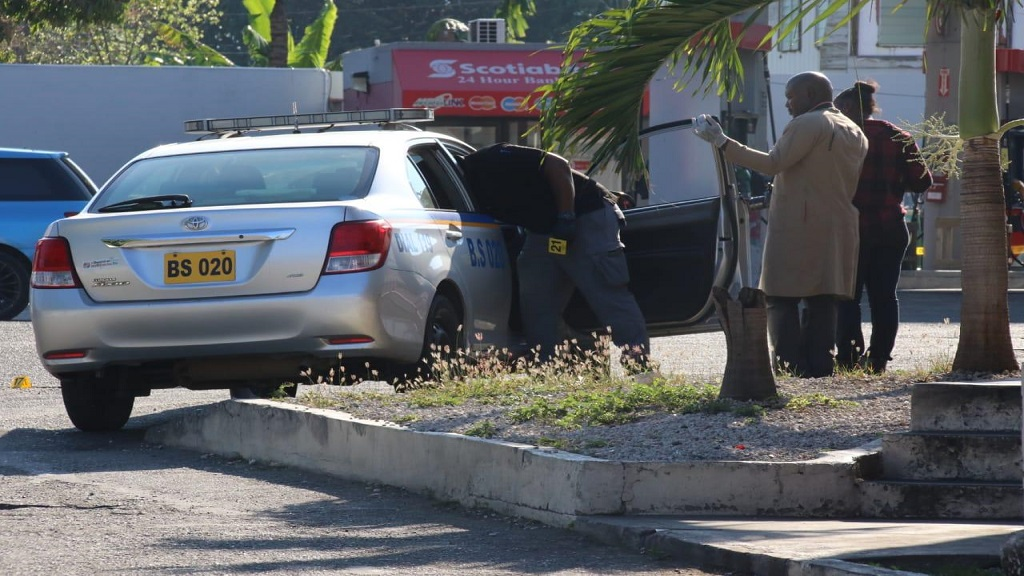 Crime scene investigators examine a police car in which a lawman was shot in St Andrew on Friday morning.