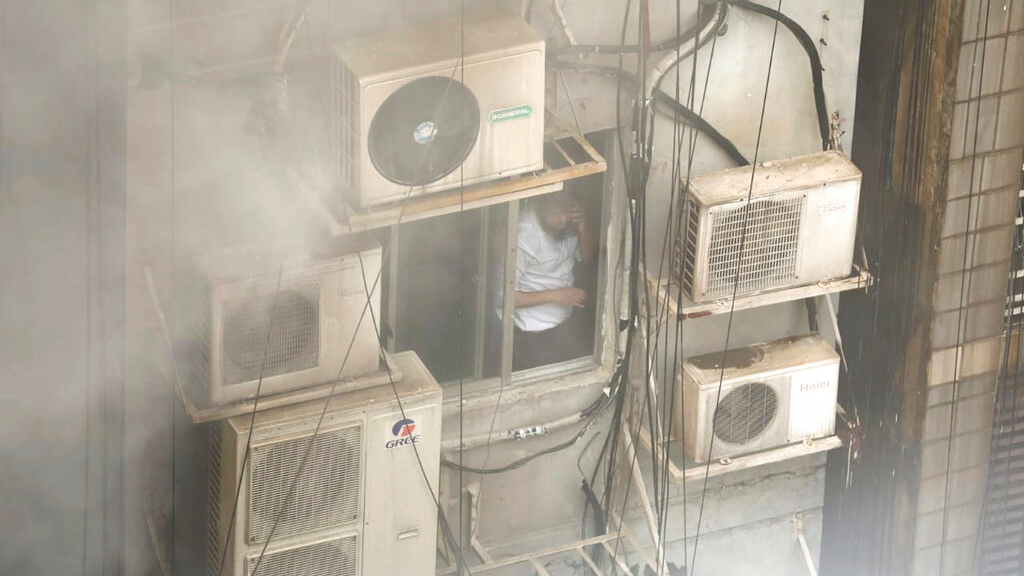 A Bangladeshi, stuck in a multi-storied office building on fire, speaks on his mobile phone in Dhaka, Bangladesh, Thursday, March 28, 2019. (AP Photo/Mahmud Hossain Opu)