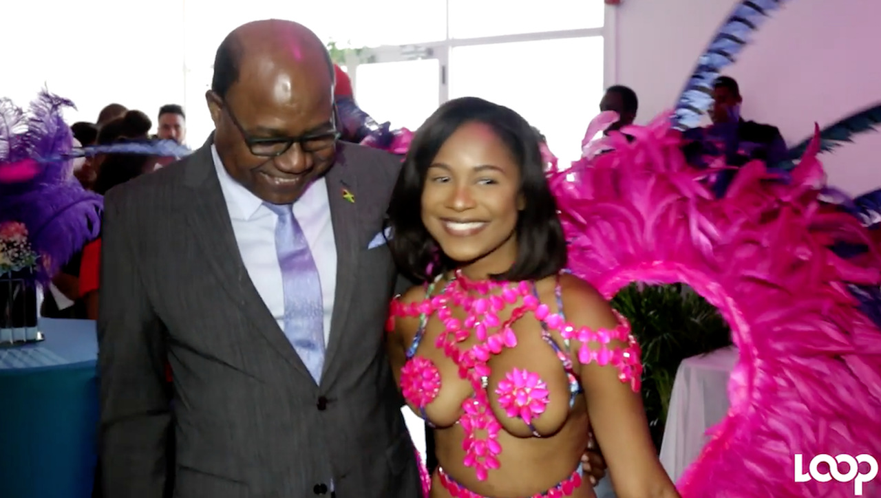 Tourism Minister Edmund Bartlett shares a laugh with a model in the Bacchanal Jamaica costume at the launch of Carnival in Jamaica on Tuesday.