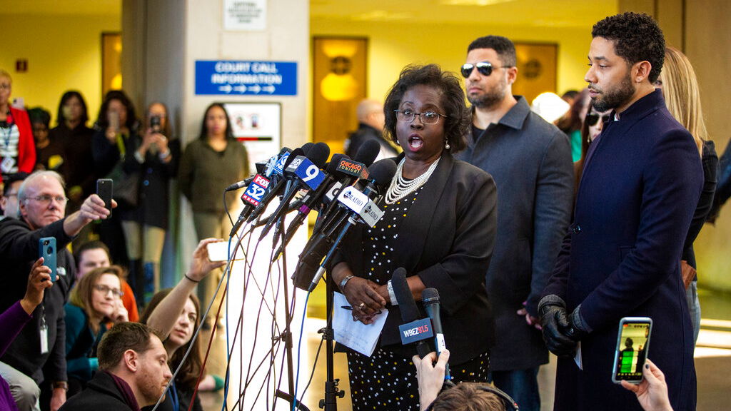 In this Tuesday, March 26, 2019, file photo, actor Jussie Smollett, right, listens as his attorney, Patricia Brown Holmes, speaks to reporters at the Leighton Criminal Courthouse after prosecutors dropped all charges against him.  (Ashlee Rezin/Chicago Sun-Times via AP, File)