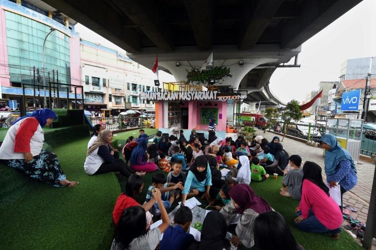 Une bibliothèque de rue installée sous une voie rapide automobile, le 10 février 2019 à Jakarta, en Indonésie