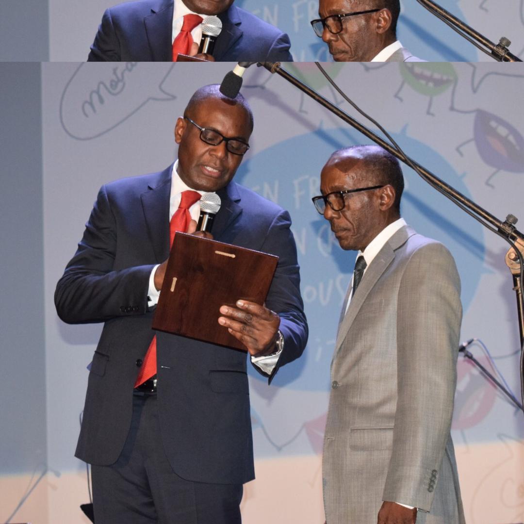Evens Emmanuel recevant, le mercredi 20 mars, sa plaque Honneur et Mérite à l'occasion de la Journée Internationale de la Francophonie./Photo: AUF.