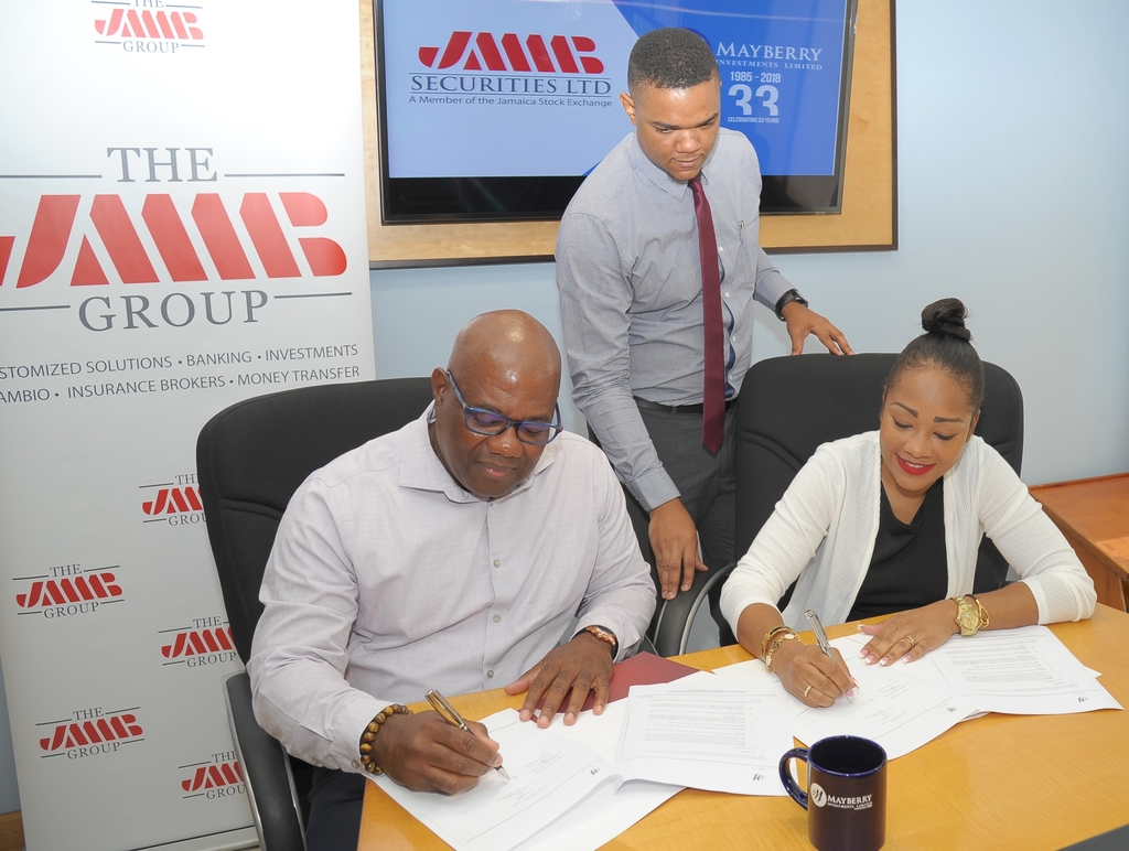Karl Townsend (left), chief country officer, JMMB Capital Markets and Tania Waldron-Gooden (right), director of Investment Banking, Mayberry Investments Limited 'inks the deal', under the keen eye of Mckoy Jackson, senior manager of investment banking at Mayberry at that company's head office.