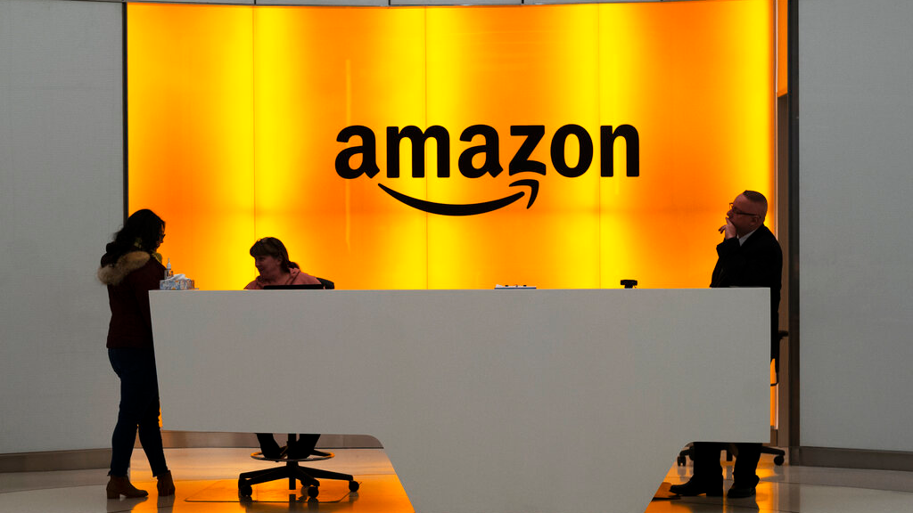 FILE - In this Feb. 14, 2019 file photo, people stand in the lobby for Amazon offices in New York. Amazon is providing a tool that will allow brands to remove listings from its site themselves that they consider to be for counterfeit goods. The online giant is also launching a product serialization service, which allows brands to put unique codes on their products during the manufacturing process. The codes are then scanned by Amazon to confirm authenticity once purchased. (AP Photo/Mark Lennihan, File)