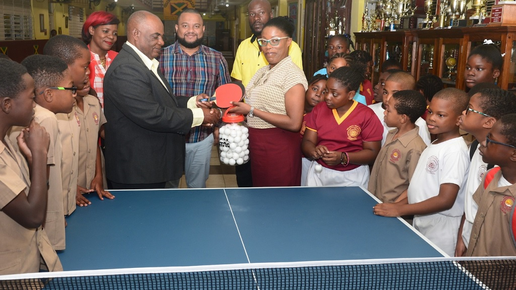 Godfrey Lothian, President, Table Tennis Jamaica, makes a presentation of table tennis rackets, balls and a table to Janet Howard, Principal, Wolmer's Preparatory School at the institution on Monday, March 4, 2019. Along with curious students, others looking on (from left) are PTA President Lisa Reynolds, Board Chairman Ryan Foster and coach Raymond Leveridge.