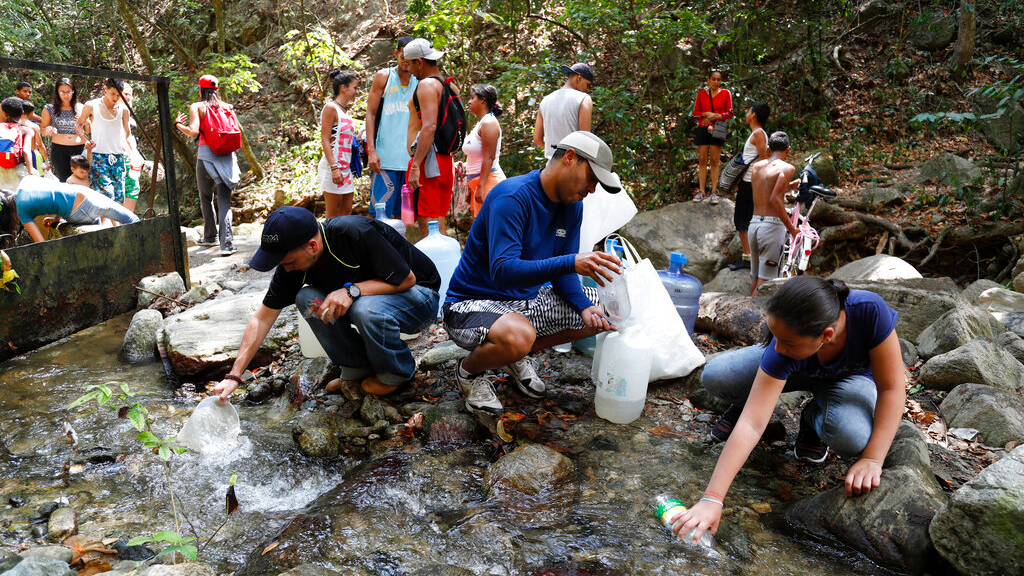 People collect water from a stream in Avila National Park during rolling blackouts, which affects the water pumps in people's homes and apartment buildings, in Caracas, Venezuela, Sunday, March 10, 2019.  (AP Photo/Eduardo Verdugo)