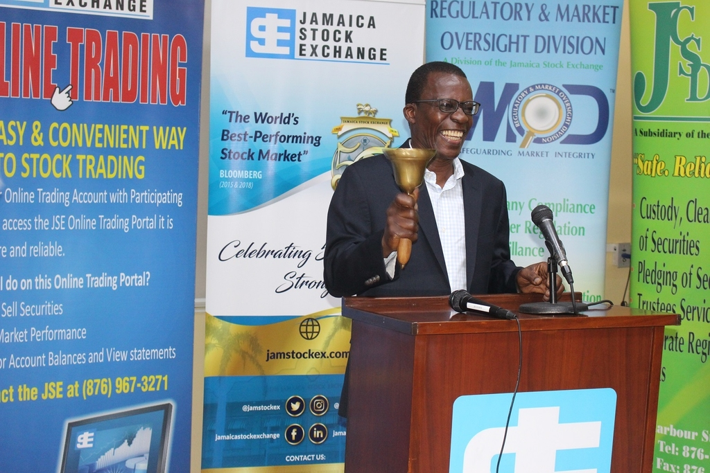 Dr. Lawrence Nicholson, Author and Publisher of 'Understanding the Caribbean Enterprise: Insights from MSMEs and Family Owned Businesses' participates in the ceremonial ringing of the bell at the Jamaica Stock Exchange.