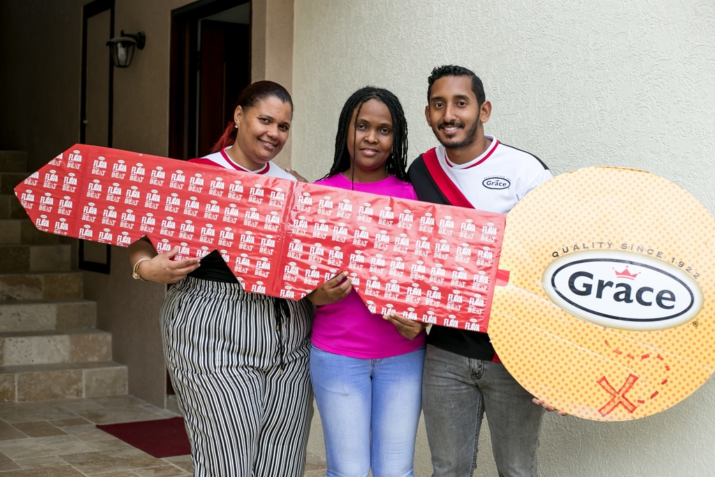 Jillian Herons, Promotions Coordinator, Grace Foods (L) and VJ Tolan, Assistant Global Category Manager, Grace Foods (R) flank Artens Whyte (centre) who is the first to qualify in Round One of the Grace Winna House competition to compete for a $14 million Brand New House Courtesy of Grace Foods.