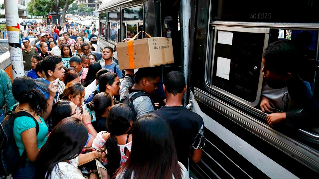 Locals scramble to board a bus after a power outage in Caracas, Venezuela, Thursday, March 7, 2019. (AP Photo/Eduardo Verdugo)