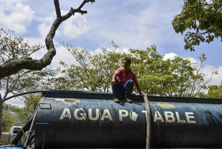 Un camion-citerne remplit d'eau potable en attente d'être distribuée après une panne d'électricité massive, le 13 mùars 2019 à Caracas, au Venezuela