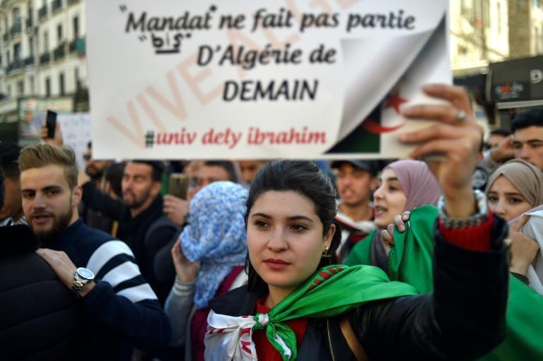"""Un étudiant algérien brandit un """"4+"""" barré en signe de protestation contre la prolongation du 4e mandat du président Abdelaziz Bouteflika, le 12 mars 2019 à Alger"""
