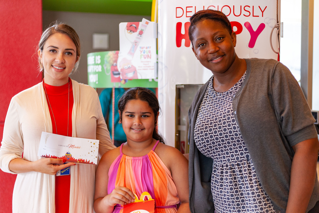 Kristie Farfan, Social Media and Marketing Coordinator, MovieTowne, and Kalifa Duncan, Market Supervisor, McDonald's , present a young winner with her movie ticket