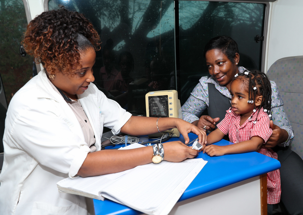 Personal Banking Officer, Ochio Rios Branch, Sagicor Bank, Christine Gordon-Wynter (right), helps Nurse Sheshanna Simpson to administer an oxygen saturation test to young Hillary Walker, during a health tour at the Tobolski Basic School in Browns Town.