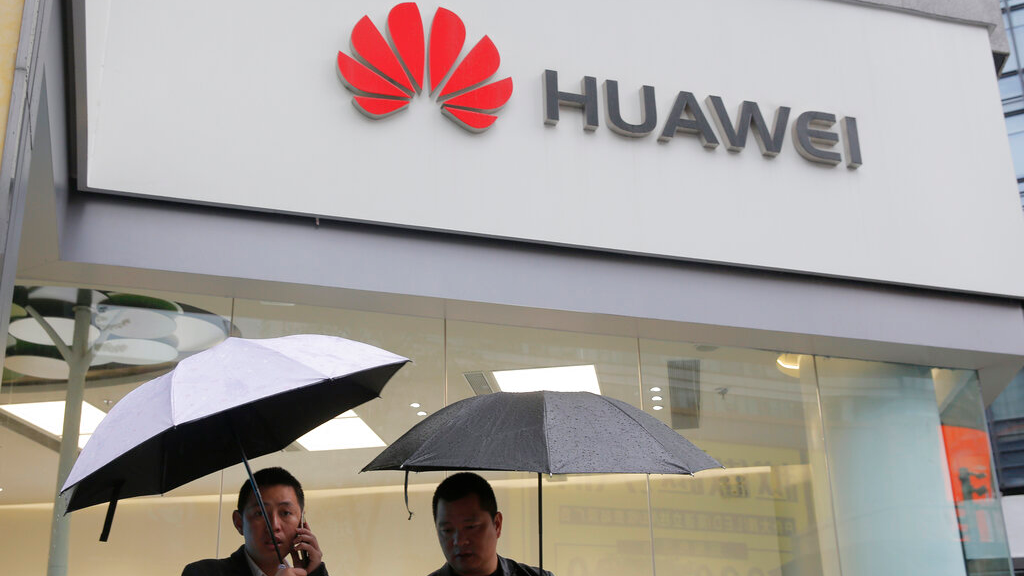 In this Thursday, March 7, 2019 file photo, two men stand outside a Huawei retail shop in Shenzhen, China's Guangdong province. (AP Photo/Kin Cheung, File)