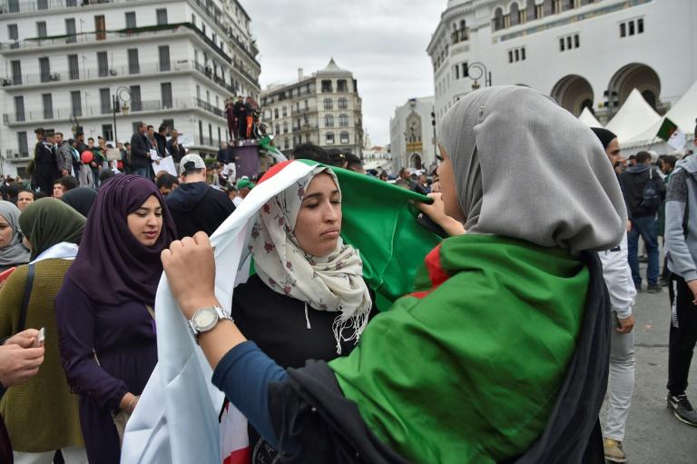 """Des manifestants dans le centre d'Alger arborent le 8 mars 2019 des pancartes sur lesquelles est écrit """"Non à un cinquième mandat"""", alors qu'ils protestent contre la candidature d'Abdelaziz Bouteflika pour la présidentielle d'avril"""