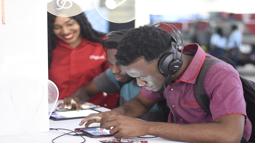 Students fill out internship applications inside the Digicel booth during a recent career expo at UWI. (PHOTOS: Marlon Reid)
