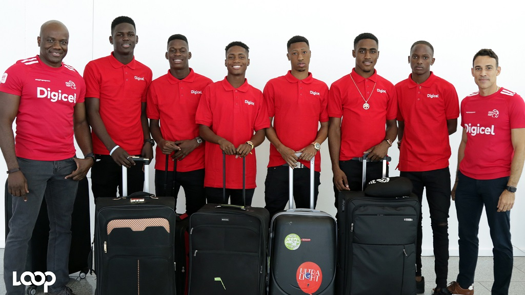 Digicel Jamaica's CEO, Justin Morin (right) and Public Relations and Communications Manager Elon Parkinson (left) pose with six of the seven players who will participate in a football camp at Stoke City Football Club in England. Digicel hosted the players at its headquarters in downtown Kingston on Friday, March 22, 2019. (PHOTOS: Ramon Lindsay).