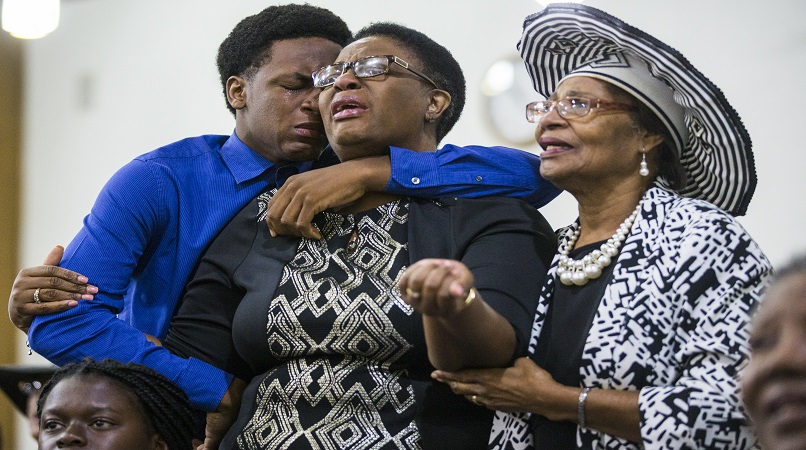 Brandt Jean and his mother Allison Jean, who are the brother and mother of Botham Jean mourn with another churchgoer during a prayer service for Jean at the Dallas West Church of Christ on Sunday, Sept. 9, 2018 in Dallas. (Shaban Athuman/The Dallas Morning News via AP)