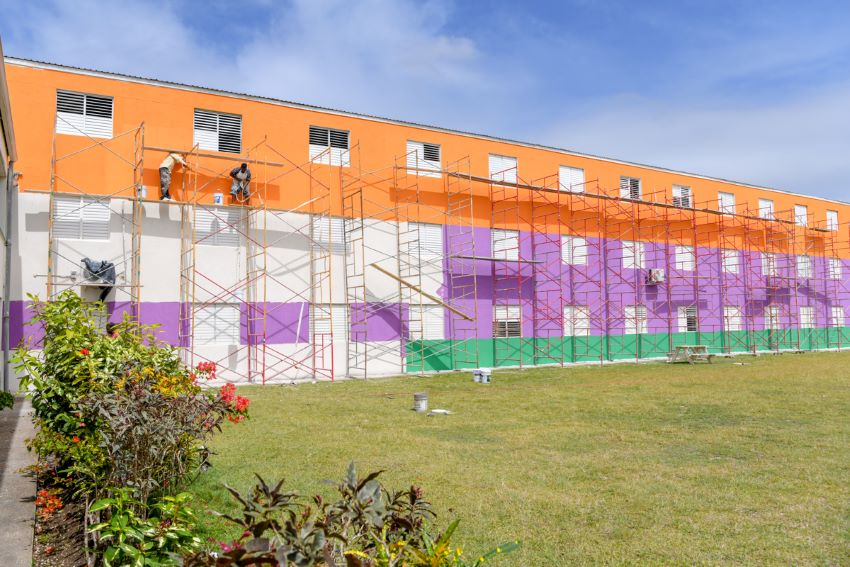The main classroom block at St. George Secondary being painted in bright colours by workmen.  (Ministry of Education, Technological and Vocational Training)