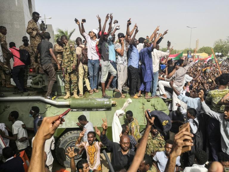 Des manifestants en liesse, grimpés sur un char, font le signe de la victoire, lors d'un rassemblement devant le quartier général de l'armée, le 11 avril 2019 à Khartoum, au Soudan