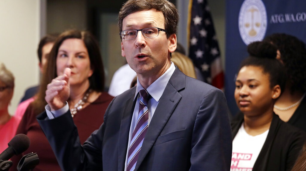 "Photo: In this Feb. 25, 2019 file photo, Washington state Attorney General Bob Ferguson speaks at a news conference announcing a lawsuit challenging the Trump administration's Title X ""gag rule"" in Seattle. A federal judge in Washington state on Thursday, April 25, 2019, will hear arguments in two cases against new Trump administration rules that could cut off federal funding for health care providers who refer patients for an abortion. (AP Photo/Elaine Thompson, File)."