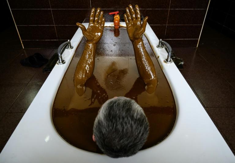 Un homme immergé dans une baignoire remplie de pétrole brut, un traitement classique à Naftalan en Azerbaïdjan, le 21 mars 2019