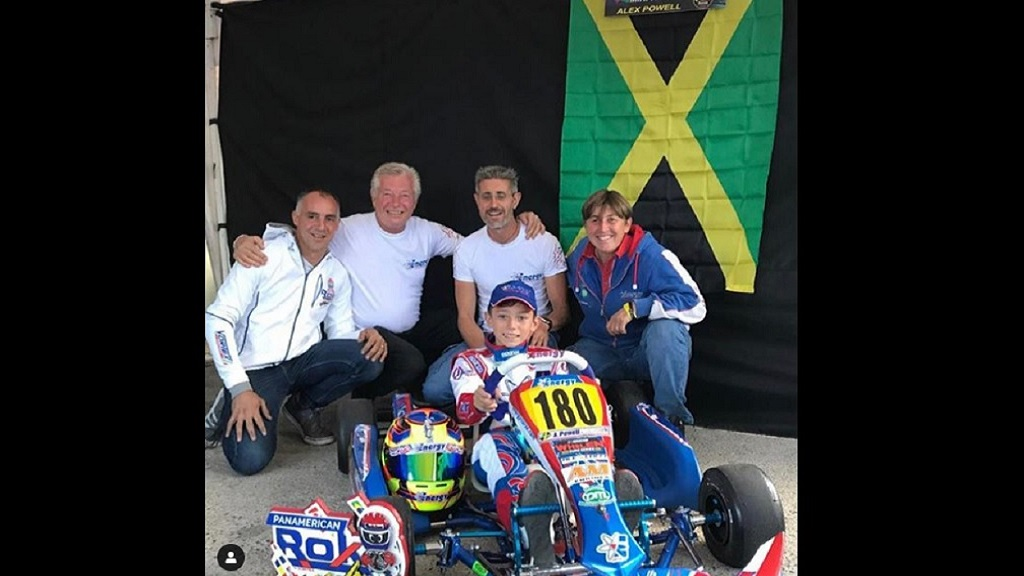 Eleven-year-old  karter Alex Powell and his support team pose in front of a Jamaican flag