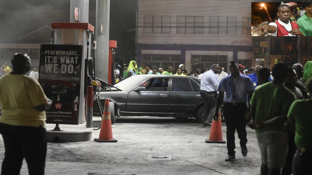 People stand around the crashed motor car at the Braham's Texaco service station in Port Antonio, Portland on Thursday night. (INSET: Service station attendant Brandon Harris, whose action averted the fire from spreading). (PHOTOS: Marlon Reid)