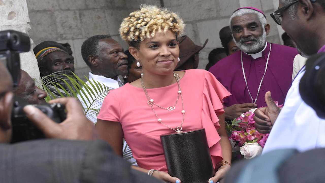 Melissa Rickards carries the urn bearing the remains of her mother, Dorraine Samuels-Binger after a funeral service at the University Chapel in St Andrew on Monday. (PHOTOS: Marlon Reid)