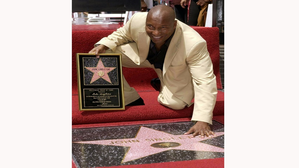 In this August 26, 2003 file photo, director John Singleton touches his new star on the Hollywood Walk of Fame in Los Angeles. (AP Photo/Nick Ut, File)
