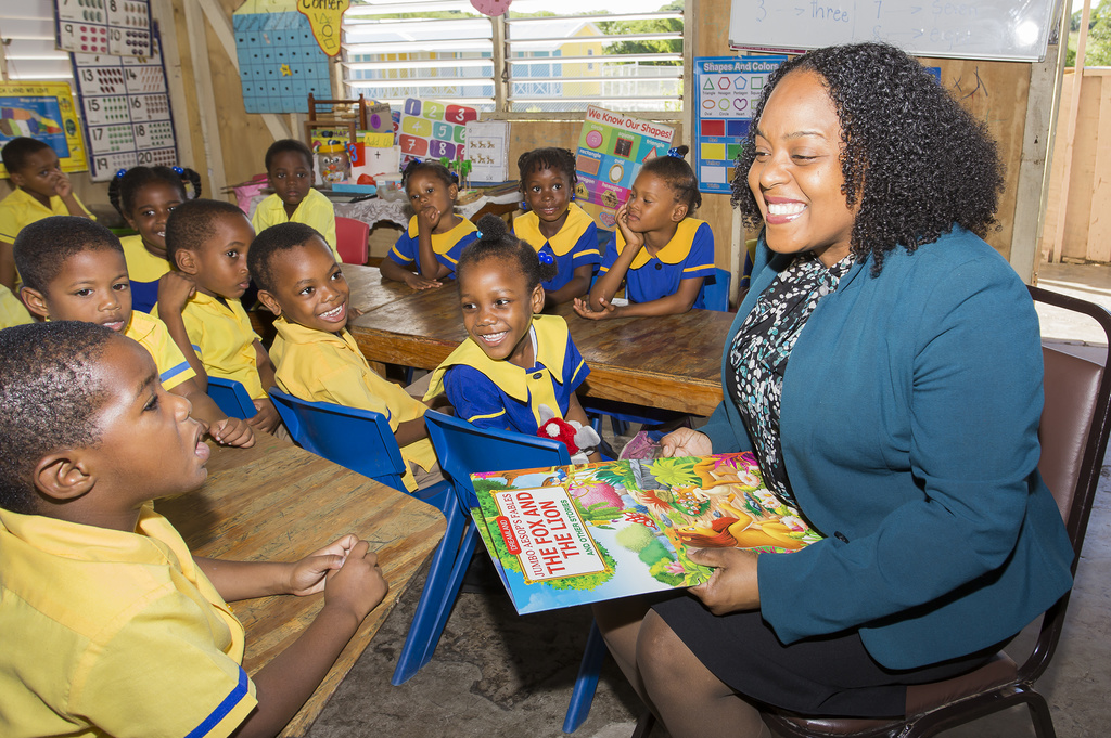 Melissa McArthur, Manager, Personal Credit Services, CIBC FirstCaribbean International Bank with students of Freetown All Age School following a reading session.