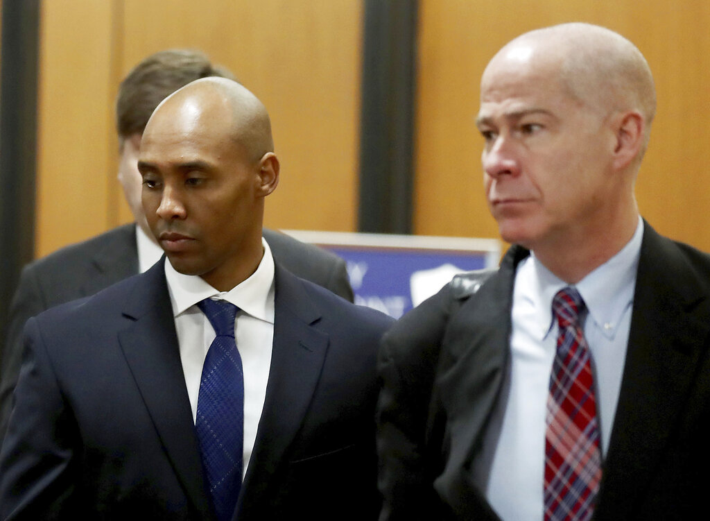 Former Minneapolis police officer Mohamed Noor, center, is accompanied by his attorneys Peter Wold, not pictured, and Thomas Plunkett, right, as he walks towards the Hennepin County Government Center for opening arguments of his trial Tuesday, April 9, 2019, in Minneapolis Opening arguments scheduled to begin in the trial of former Minneapolis police officer Mohamed Noor in the shooting death of Justine Ruszczyk Damond. (David Joles/Star Tribune via AP)