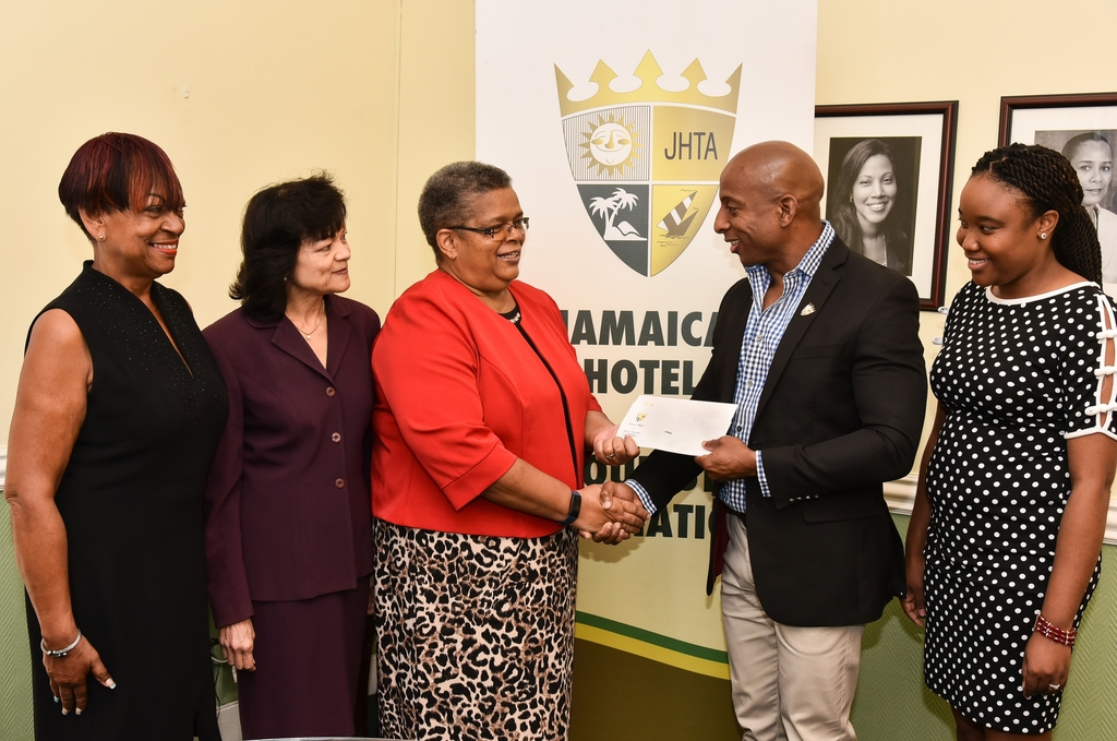 Omar Robinson (2nd right), President of the Jamaica Hotel & Tourist Association (JHTA) presents Carol Palmer (3rd left), Chair, National Task Force Against Trafficking in Persons with the two cheques.  Joining in (l-r) were Vana Taylor, 1st Vice President, JHTA; Camille Needham, Executive Director, JHTA and Chenee Russell, Manager, Trafficking in Persons Secretariat, Ministry of Justice.